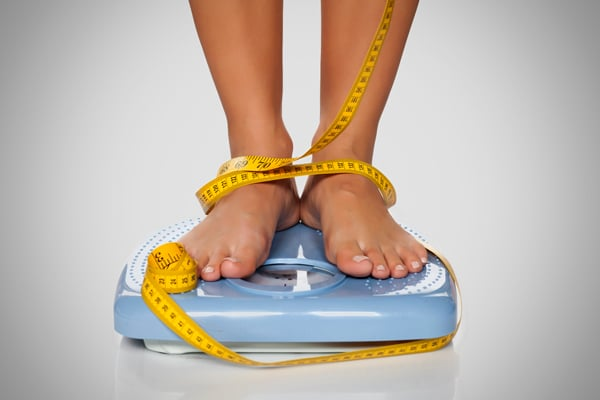 Woman Standing on Bathroom Scales With a Measuring Tape Wrapped Around Her Feet